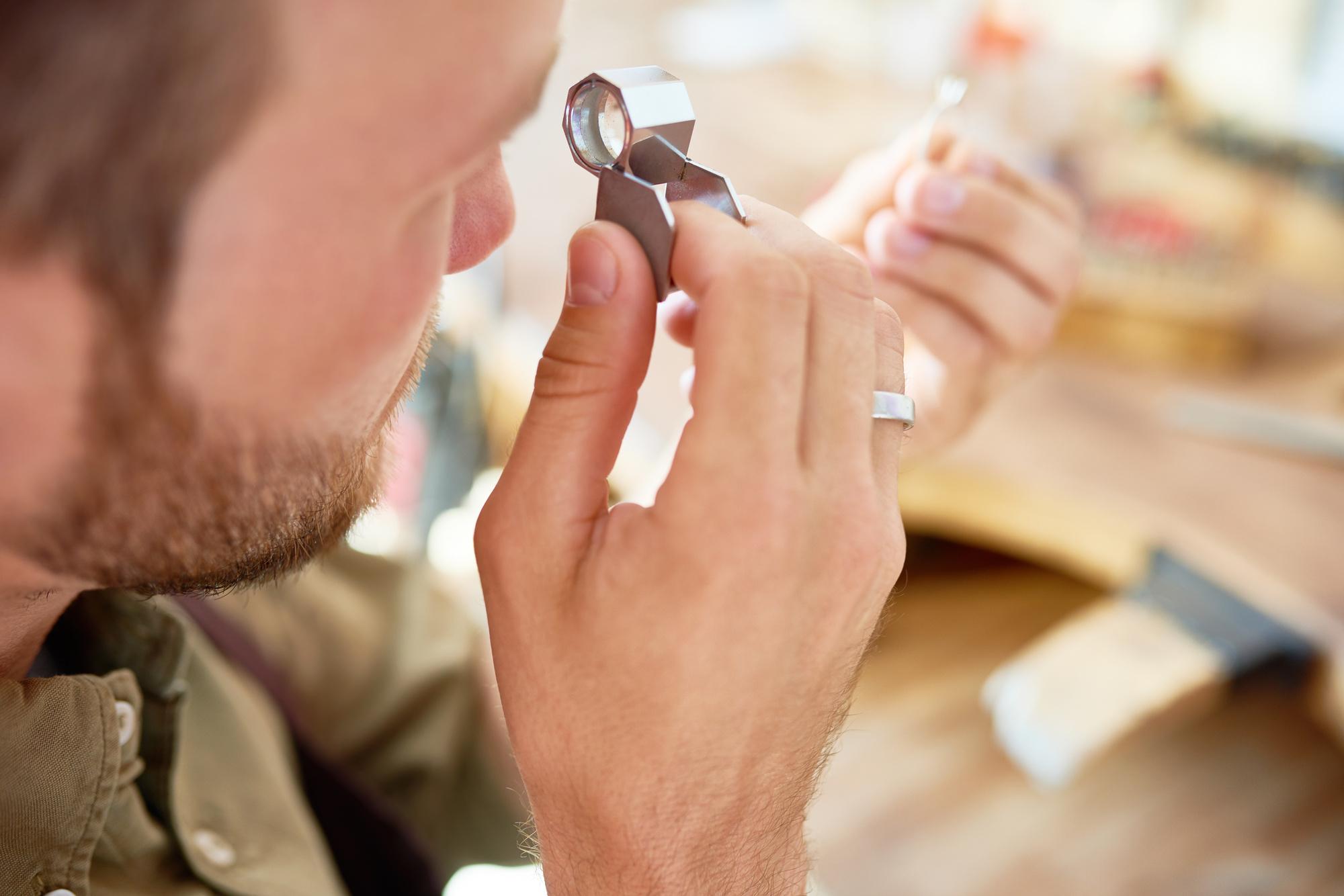 man at pawnshop appraising ring