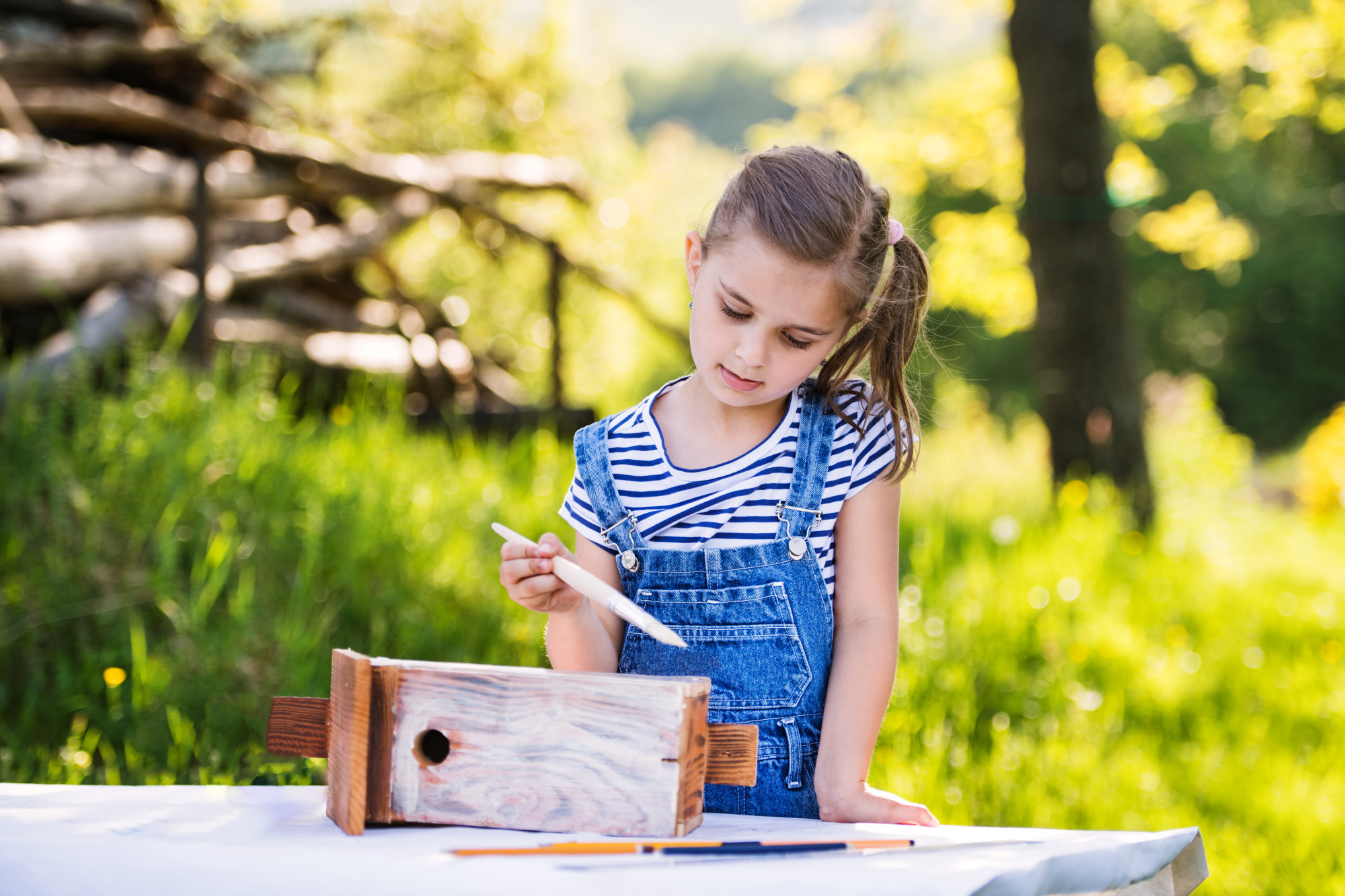 girl painting birdhouse outdoors
