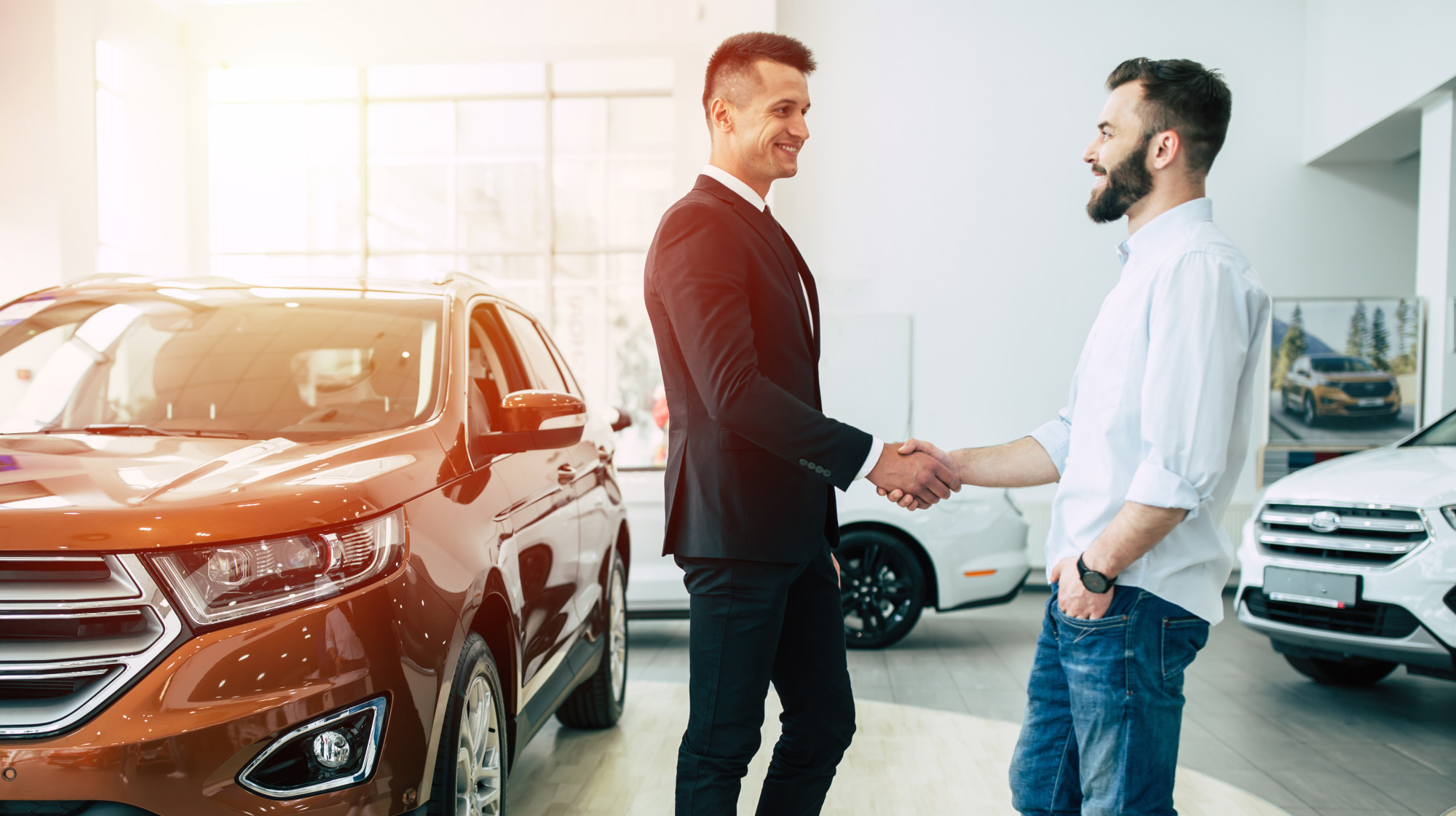car salesman shaking hands with customer