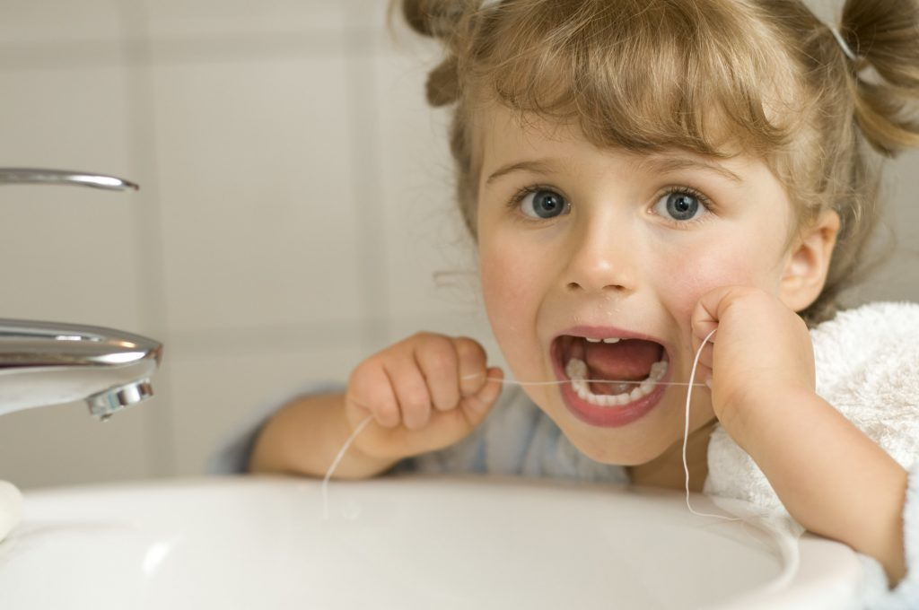 Child Flossing Her Teeth