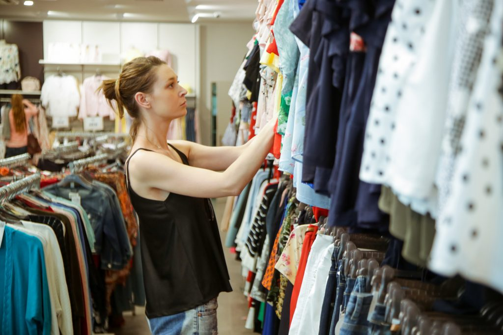 Woman Choosing Clothes on a Clothing Shop